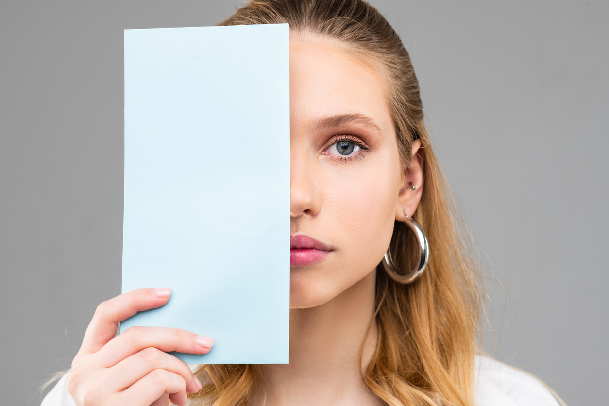 Woman covering half of her face with paper seeking causes of uneven eyes